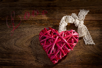 red wooden heart with lace bow on wood and love written