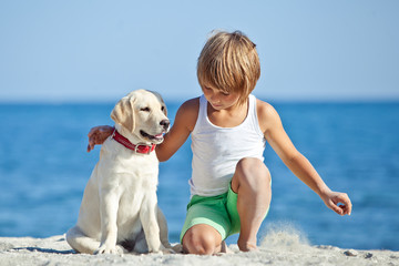 Happy kid with a dog on the beach