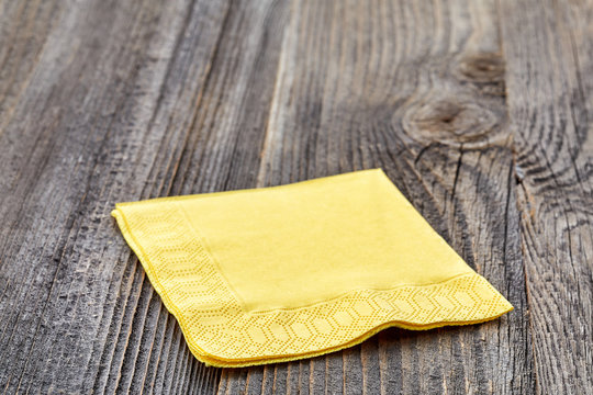 Yellow napkin on wooden table isolated