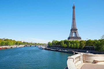 Eiffel tower and empty white balustrade on Seine river in a clear day