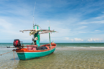Samroiyod Beach, fishing boat parked on beach, background is blue sky