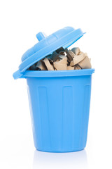 A blue bin full of crumpled paper, isolated on white background