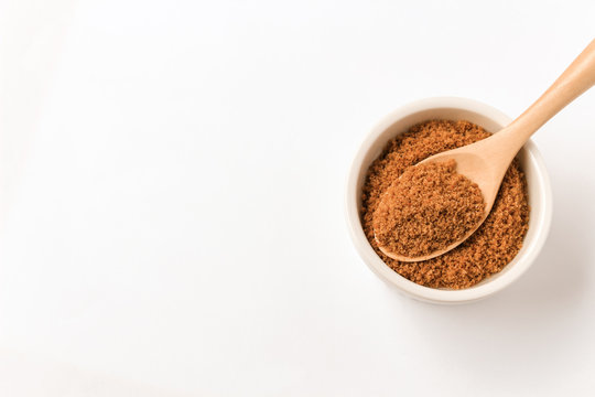 Coconut sugar in a cup with white background