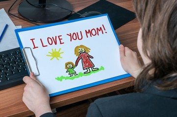 Business woman (mother) in office holds greeting card from her child with message I love you mom.