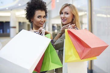 Waist up of two turning women with shopping bags