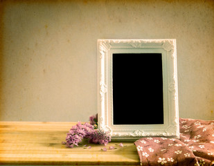 White vintage photo frame with sweet  flower on  wooden table