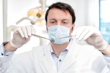 junger zahnarzt mit mundspiegel und zahnsonde