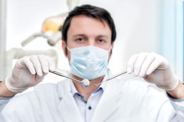 freundlicher zahnarzt präsentiert seine werkzeuge