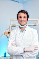 junger fröhlicher zahnarzt in der zahnarztpraxis