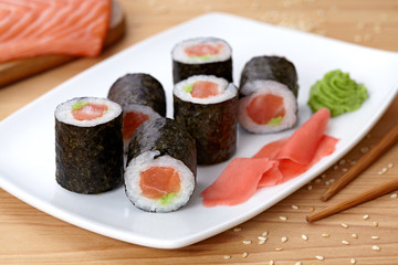 Maki sushi roll with salmon, wasabi, ginger and nori seaweed.