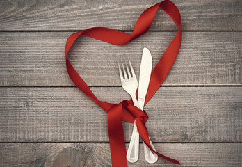 Heart shape ribbon and kitchen silverware.