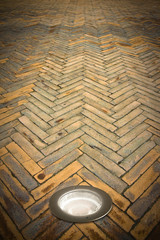 Recessed floor lamp on terracotta floor - image with copy space