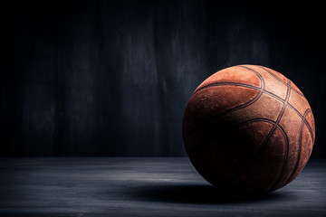 Old basketball ball on a black background