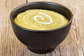 vegetable mash in black bowl on wooden table