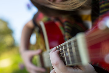 Fingers on the strings close up, girl playing acoustic guitar.