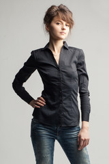 Young beautiful caucasian woman in black shirt and jeans on gray background
