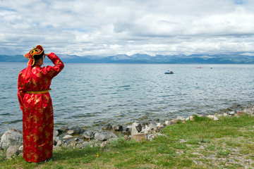 Women in traditional clothes looking at lake