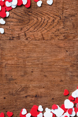 Valentines Day background with heap of small hearts on wooden background. Copy space for your text