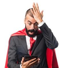 Super hero businessman holding a tablet