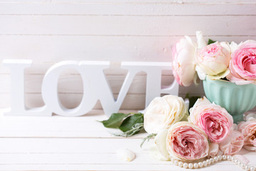 Pink roses flowers in vase and word love  on white painted woode