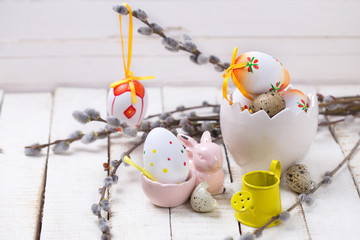 Decorative Easter eggs in bucket, willow  branches  and rabbit