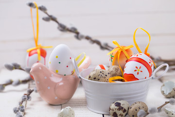 Colorful easter eggs in bucket, decorative bird and willow  bran