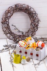 Decorative  Easter eggs in box, willow  branches on  white woode