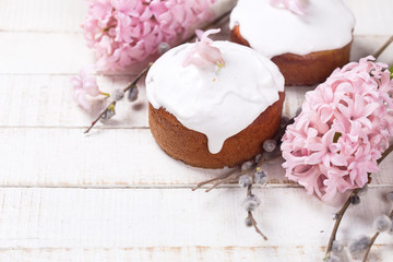 Easter cakes, pink hyacinths, willow branches on white wooden ba