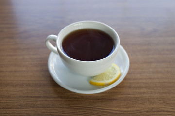 White cup of tea on a saucer with a slice of lemon on it