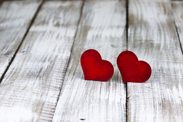 Two red wooden hearts on white rustic wood background