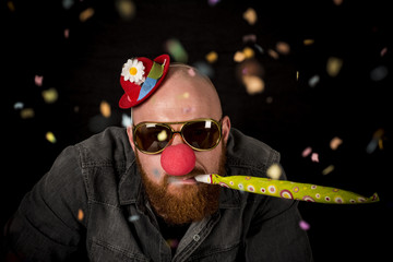 Man with beard wearing red nose, sunglasses and funny hat