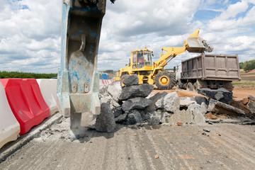 Large jackhammer breaking street asphalt paving during road construction works