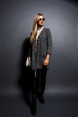Sexy Beauty Girl. Fashion Blonde. Portrait of a girl dressed in grey coat and sunglasses, wearing a beige bag posing on a grey background.