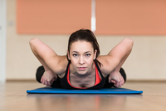 Young sports woman practicing yoga Pose. Indoor gym.