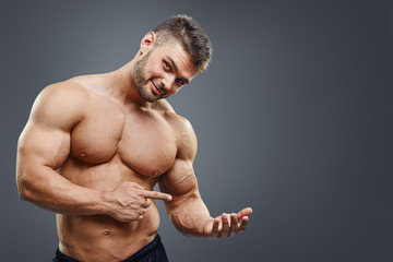 shirless muscular man holding copy space