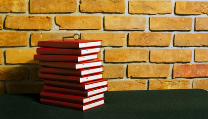 Stos czerwonych książek i klucz na tle ściany z cegły.