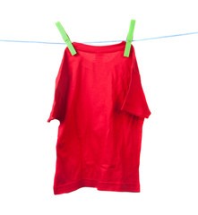 red T-shirt drying on a rope on a white background