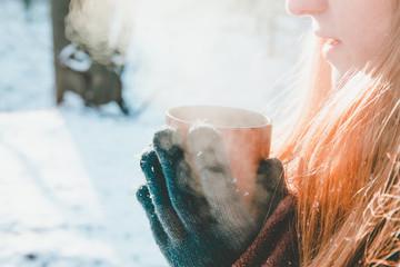 Junge Frau trinkt warmes Getränk