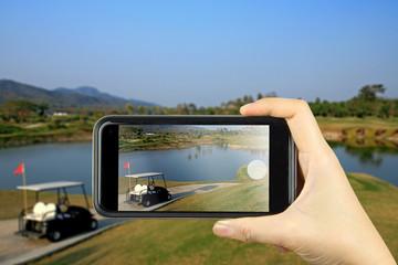 Taking photo on smart phone. Golf club.