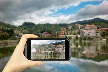 Taking photo on smart phone. building along lake in sapa city,