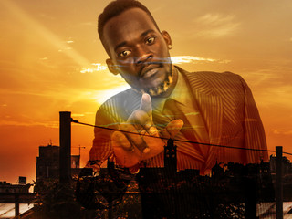 Double exposure of man using interactive multimedia board and city sunset