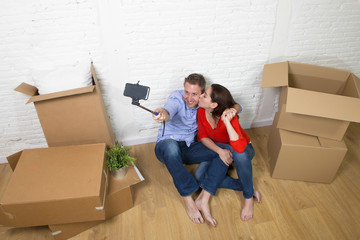 young happy American couple sitting on floor celebrating moving to new house taking selfie photo with mobile phone