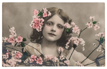 Portrait of little girl with flowers. Vintage picture
