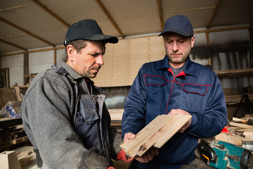 Inspector and carpenter in the carpentry workshop