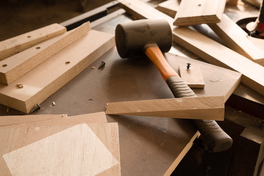Wood products and tools lie on a workbench in a workshop