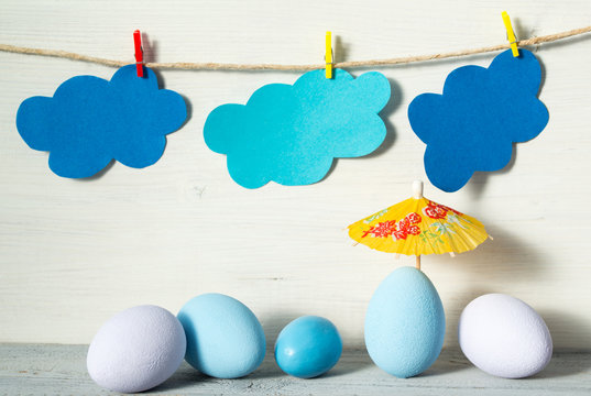 Easter eggs in pastel colors, yellow rice paper umbrella and paper clouds on a clothespins, on white wooden background