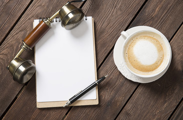 Notebook with a pen on the table next to coffee and telefon