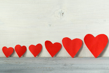 Valentines day background, red hearts in a line on a light wooden background