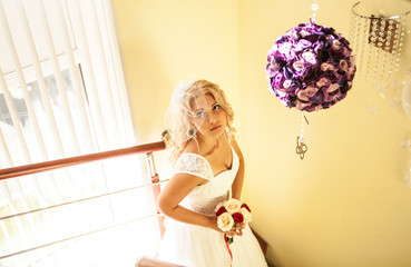 Young bride in wedding dress holding bouquet