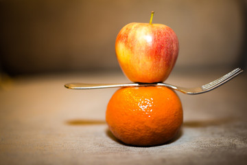 fresh apple and orange in body with fork for healthy, vitamin and diet control on shade table background